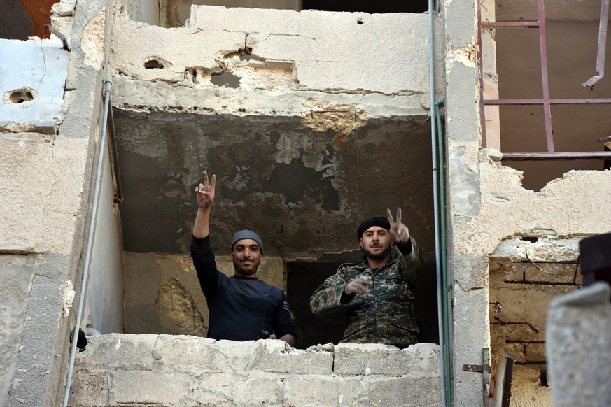 epa05650141 A handout picture made available by the official Syrian Arab News Agency (SANA) shows Syrian soldiers making a V for victory sign from a window of damaged building in Aleppo's eastern Masaken Hanano area in Aleppo province, Syria, 27 November 2016. According to SANA a military source announced on 27 November 2016 that the army units in cooperation with the supporting forces established full control over Jabal Badro neighborhood and Masaken Hanano area in Aleppo .  EPA/SANA HANDOUT  HANDOUT EDITORIAL USE ONLY/NO SALES