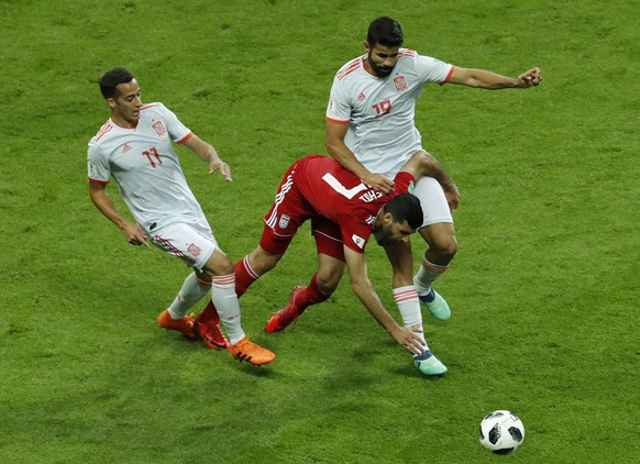 Iran's Mehdi Taremi, center, clashes with Spain's Lucas Vazquez, left, and Spain's Diego Costa during the group B match between Iran and Spain at the 2018 soccer World Cup in the Kazan Arena in Kazan, Russia, Wednesday, June 20, 2018. (AP Photo/Eugene Hoshiko)