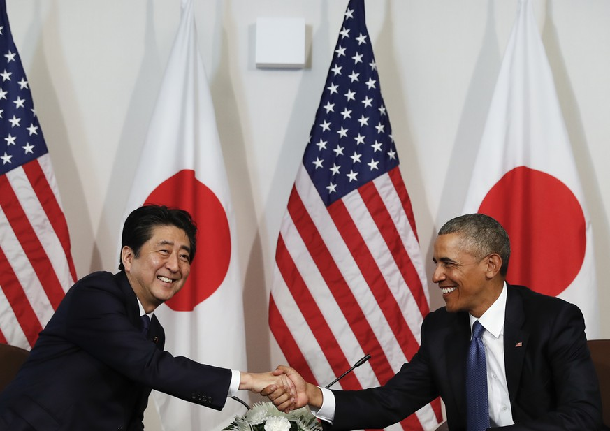 President Barack Obama and Japanese Prime Minister Shinzo shake hands as they are photographed at the start of a bilateral meeting at Camp H.M. Smith, Hawaii, Tuesday, Dec. 27, 2016. (AP Photo/Carolyn Kaster)