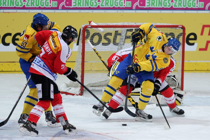 Sweden's Ted Brithen, right, and Andreas Thuresson, left, fights for the puck against Switzerland's Dominik Schlumpf, during a test game Switzerland against Sweden in Arosa, Switzerland, Friday, April 11, 2014.  (PHOTOPRESS/Arno Balzarini)