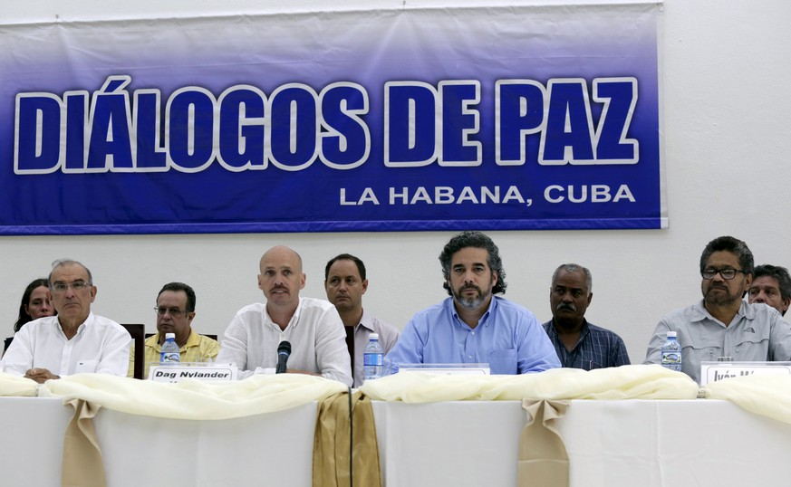 Colombia's lead government negotiator Humberto de la Calle (L) and Colombia's FARC lead negotiator Ivan Marquez (R) sit as mediators Dag Nylander of Norway (2nd L) and Rodolfo Benitez of Cuba read a joint declaration in Havana July 12, 2015.  Colombia's government pledged on Sunday to de-escalate military actions against leftist guerrillas beginning July 20 if the rebels make good on their pledge of a unilateral ceasefire from that date. The commitment, issued in a joint statement with rebels of the Revolutionary Armed Forces of Colombia (FARC) in Havana, provides a boost to peace talks that have been threatened by increased battlefield violence in recent months. REUTERS/Enrique de la Osa