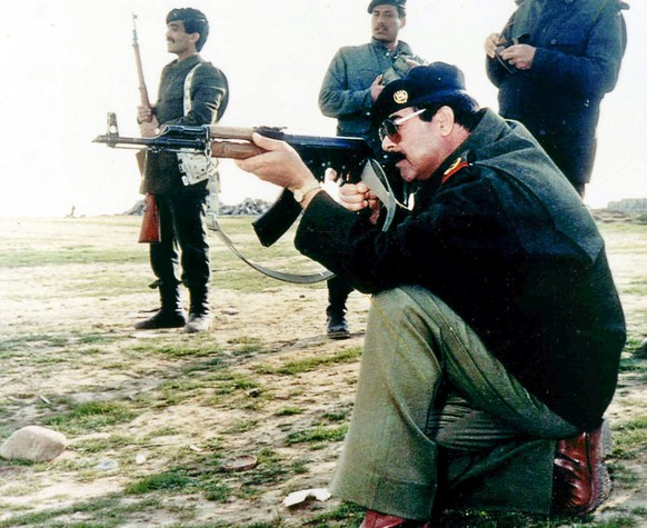 This is an undated photo of former Iraqi ruler Saddam Hussein firing an AK-47 in Iraq. The old men of Saddam Hussein's old guard have been nabbed in dead-of-night raids, hiding in bedrooms, or scampering on rooftops. To date, U.S. troops have whittled a list of 55 top fugitives down to just 21, but Saddam and his two sons remain elusive. (KEYSTONE/AP Photo)