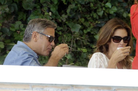 George Clooney and Cindy Crawford drink as they sit in the garden of the Cipriani hotel in Venice, Italy, Saturday, Sept. 27, 2014. Clooney, 53, and Amal Alamuddin, 36, are expected to get married this weekend in Venice, one of the world's most romantic settings. (AP Photo/Andrew Medichini)