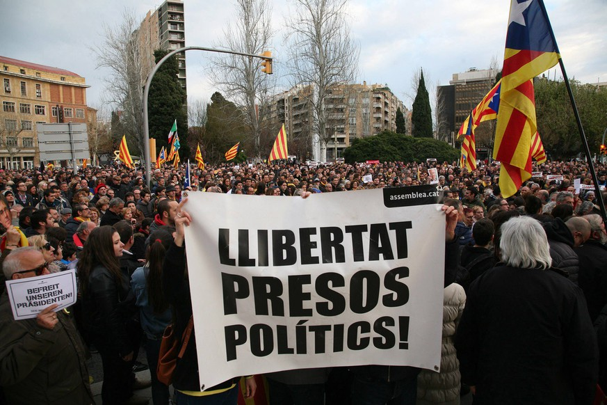 epa06629508 Protesters hold a sign reading 'Freedom for political prisoners' during a protest against the imprisonment of former Catalan leader Carles Puigdemont in Tarragona, Catalonia, north eastern Spain, 25 March 2018. According to reports, German police on 25 March 2018 allegedly detained former Catalan leader Puigdemont after he crossed into Germany from Denmark. Puigdemont is sought by Spain who issued an European arrest warrant against the former leader who is living in exile in Belgium.  EPA/JAUME SELLART