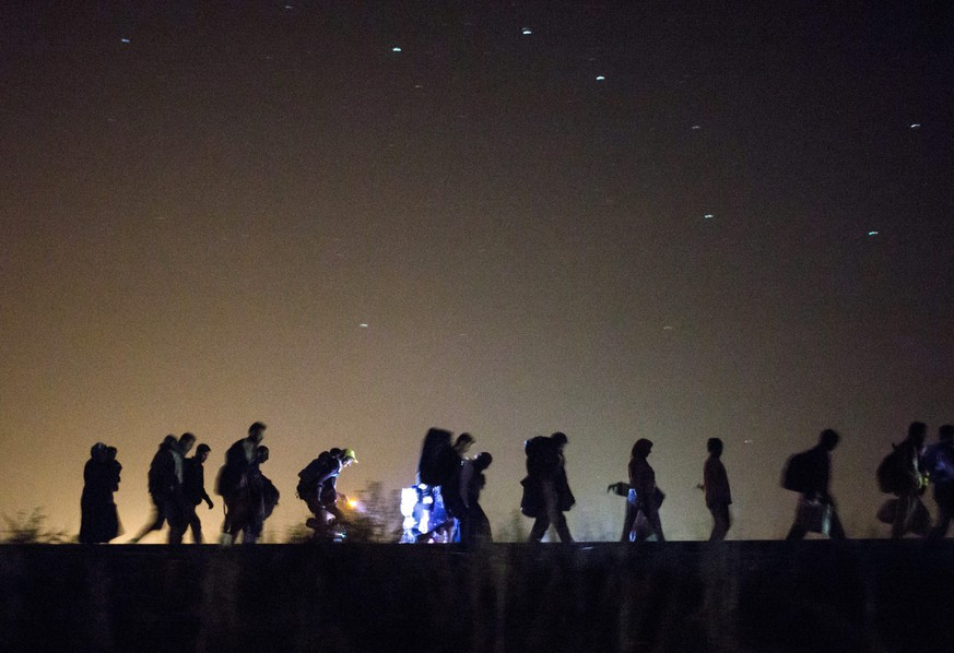 epa04929648 Migrants walk towards a checkpoint along the railway tracks connecting Horgos and Szeged near Roszke, in the vicinity of the border between Hungary and Serbia, 13 September 2015. Further along the route, Germany imposed emergency border controls with Austria to stem the tide of refugees, Interior Minister Thomas de Maiziere said Sunday, as train service from Austria to Germany was halted.  EPA/BALAZS MOHAI HUNGARY OUT