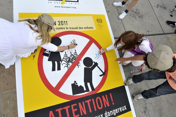 School children of the Canton of Geneva sign a banner against the child labour one day before the World Day Against Child Labour, at the Place des Nations in front of the European headquarters of the United Nations in Geneva, Switzerland, Friday, June 10, 2011. (KEYSTONE/Martial Trezzini)..