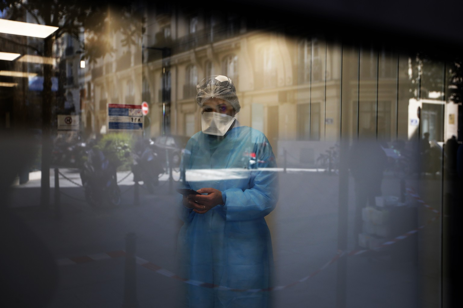 Biologist doctor Caroline Gutsmuth gives a phone call in medical biology laboratory who opened a coronavirus drive-thru testing site, in Neuilly-sur-Seine, near Paris, March 23, 2020. (AP Photo/Christophe Ena)