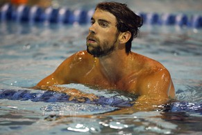 Michael Phelps looks at the score board after winning the 100-meter butterfly in the at the Arena Grand Prix swim meet in Charlotte, N.C., Friday, May 16, 2014. Phelps won the race with a time of 52.13. (AP Photo/Nell Redmond)