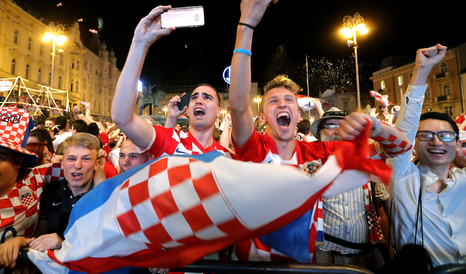 epa06814542 Croatian national soccer team fans celebrate winning he FIFA World Cup 2018 group D preliminary round soccer match between Croatia and Nigeria in downtown Zagreb, Croatia, 16 June 2018.  EPA/ANTONIO BAT