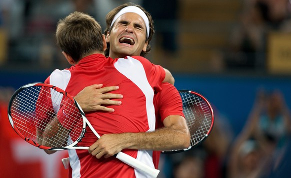 Roger Federer, right, and Stanislas Wawrinka of Switzerland react after their gold medal match against Swedish pair Simon Aspelin and Thomas Johansson at the Beijing Olympic Green Tennis Central Court for the Beijing 2008 Olympics in Beijing, China, August 16, 2008. (KEYSTONE/Alessandro Della Bella)