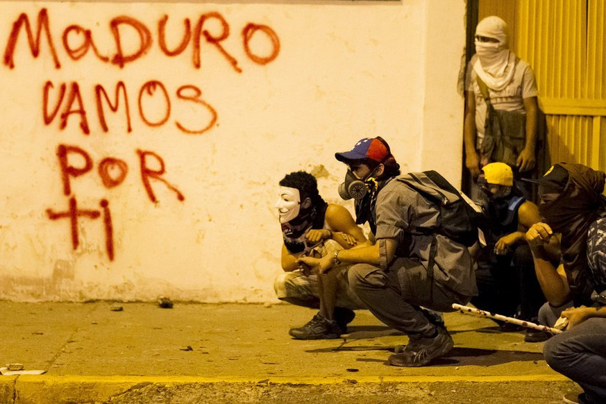 epaselect epa04099442 Masked demonstrators are seen against a wall with a graffiti reading 'Maduro we come after you' during a protest against the government of Venezuelan President Nicolas Maduro in Altamira, east of Caracas, Venezuela, 24 February 2014. Two more deaths bring the toll to 13 people killed and more than 150 injured in political violence that has gripped Venezuela since 12 February, Attorney General Luisa Ortega said on 23 February. The Venezuelan government accuses the opposition of attempting a coup d'etat to topple Maduro, who narrowly won election last year as the hand-picked successor to left-wing populist Hugo Chavez, who died in office March 2013. Opposition politician Leopoldo Lopez has been arrested as the leader of the alleged revolt. The opposition has denounced disproportionate use of force against protests and attacks on demonstrators by armed government supporters.  EPA/MIGUEL GUTIERREZ