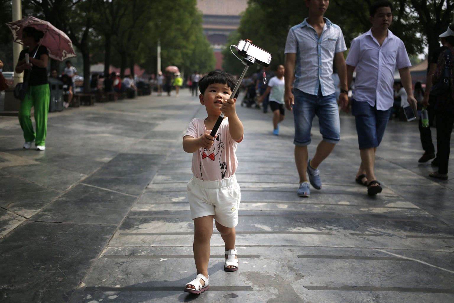 epaselect epa04778377 A Chinese boy takes a photo with a mobile phone on a selfie stick in the Forbidden City or the Palace Museum on Children's Day in Beijing, China, 01 June 2015. Normally closed on Monday, the Forbidden City opens its doors free for children under 14 in celebration of International Children's Day on 01 June.  EPA/HOW HWEE YOUNG