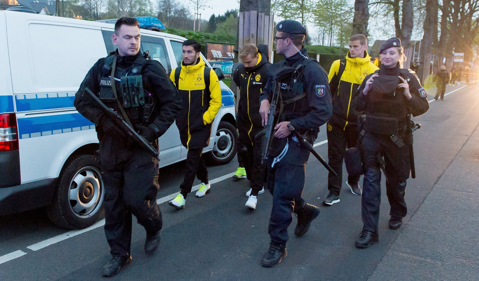 epa05903388 Borussia Dortmund players (L-R) Nuri Sahin, Marcel Schmelzer and Sven Bender are escorted by police after their team bus was hit by three explosions ahead of their UEFA Champions League soccer match against AS Monaco in Dortmund, Germany, 11 April 2017. According to reports, Borussia Dortmund's team bus was damaged by three explosions on 11 April, as it was on its way to the stadium ahead of the UEFA Champions League soccer match between Borussia Dortmund and AS Monaco. Borussia Dortmund's player Marc Bartra was injured and is hospitalized. The match has been postponed.  EPA/STR
