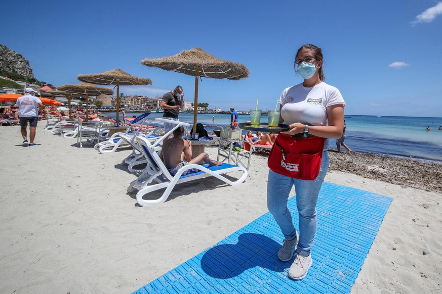 epa08469007 A waitress wearing face mask works as bathers take advantage of the first day after authorities ease the coronavirus lockdown to allow for sunbathe and to swim on the waterfront in the Mondello beach, Palermo, 06 June 2020. Several countries around the world have started to ease COVID-19 lock-down restrictions in an effort to restart their economies and help people in their daily routines after the outbreak of coronavirus pandemic.  EPA/IGOR PETYX