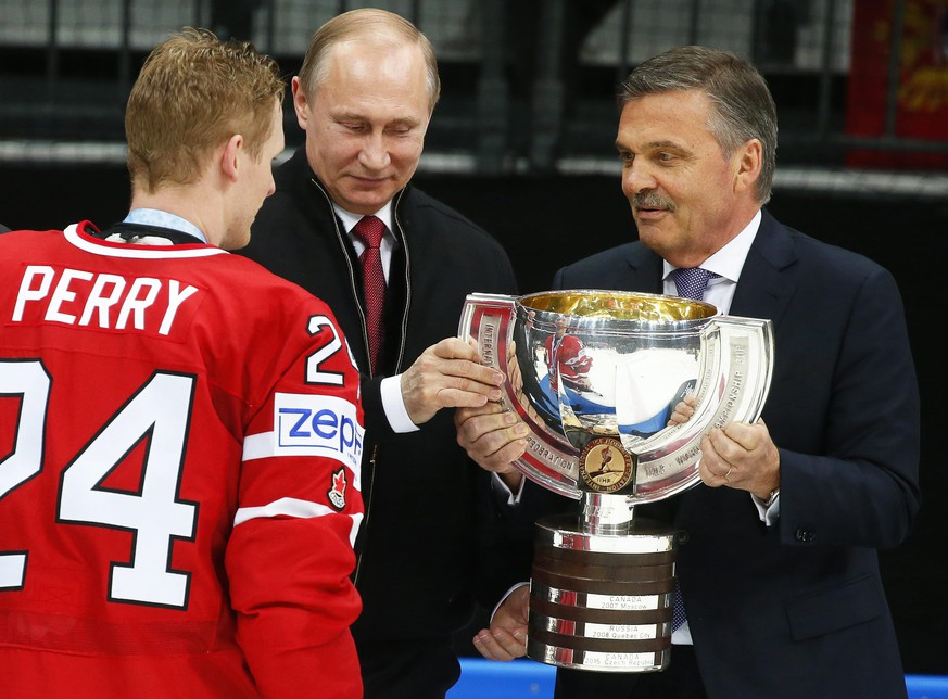epa05324221 Canada's captain Corey Perry (L) receives the trophy from Russian President Vladimir Putin (C) and Rene Fasel (R), President of the International Ice Hockey Federation, after the Ice Hockey World Championship 2016 final between Finland and Canada at the Ice Palace in Moscow, Russia, 22 May 2016. Canada won 2-0.  EPA/SERGEI ILNITSKY