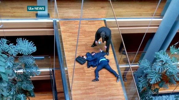 British UK Independence Party Member of the European Parliament Steven Woolfe lies on the ground  after losing consciousness in the European Parliament building in Strasbourg France Thursday Oct. 6, 2015.  Britain's fractious, right-wing U.K. Independence Party erupted into violence Thursday that left Steven Woolfe  hospitalized with a head injury after an