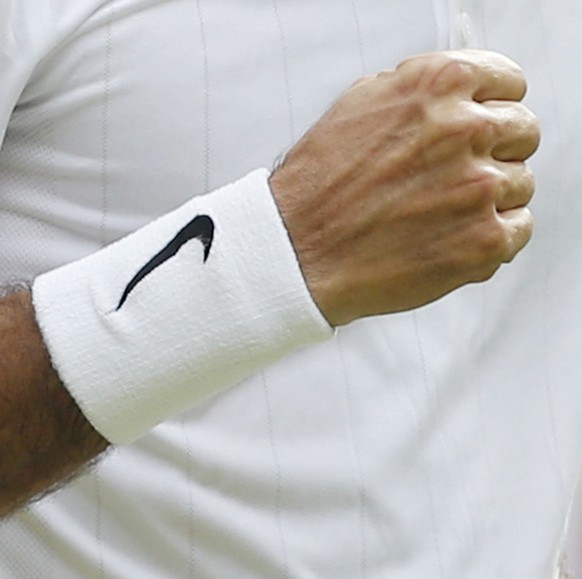 Roger Federer of Switzerland pumps a fist after winning a point against Stan Wawrinka of Switzerland during their men's singles quarterfinal match at the All England Lawn Tennis Championships in Wimbledon, London, Wednesday, July 2, 2014. (AP Photo/Pavel Golovkin)