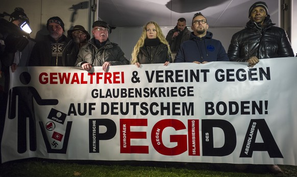 DRESDEN, GERMANY - DECEMBER 8: Supporters of the Pegida movement take part in a rally on December 8, 2014 in Dresden, Germany. Pegida is an acronym for