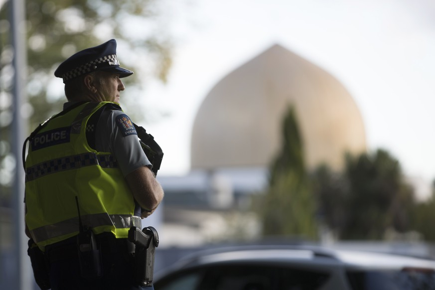 A police official stands guard in front of the Al Noor mosque in Christchurch, New Zealand, Tuesday, March 19, 2019. Christchurch was beginning to return to a semblance of normalcy Tuesday. Streets near the hospital that had been closed for four days reopened to traffic as relatives and friends of Friday's shooting victims continued to stream in from around the world. (AP Photo/Vincent Thian)
