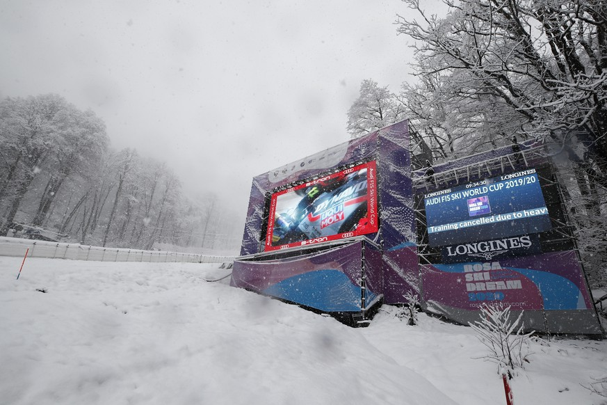 Writing on a giant screen announced that an alpine ski, women's World Cup downhill training is canceled due to heavy snow, in Rosa Khutor, Russia, Friday, Jan. 31, 2020. (AP Photo/Gabriele Facciotti)