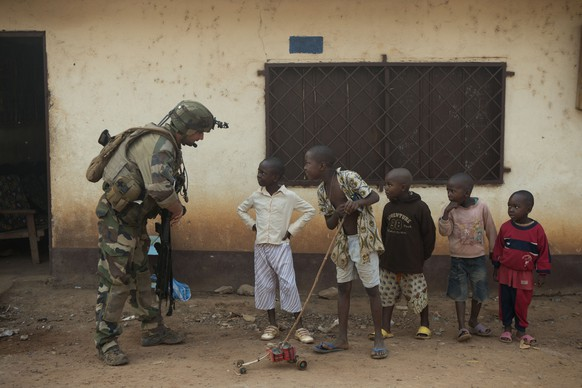 JAHRESRUECKBLICK 2014 – INTERNATIONAL – A French soldier talks to curious children as he mans a roadblock in the Miskine neighborhood of Bangui, Central African Republic, Monday, Jan. 6, 2014. (KEYSTONE/AP Photo/Rebecca Blackwell)