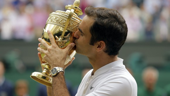 FILE - In this July 6, 2017, file photo, Switzerland's Roger Federer kisses the trophy after defeating Croatia's Marin Cilic to win the men's singles final match on day thirteen at the Wimbledon Tennis Championships in London. (AP Photo/Alastair Grant, File)