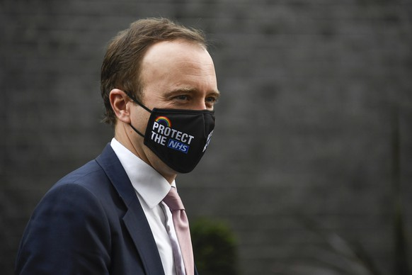 Britain's Health Secretary Matt Hancock leaves 10 Downing Street, in London, Wednesday, Dec. 16, 2020. London and some of its surrounding areas will be placed under Britain's highest level of coronavirus restrictions beginning at 00:01 local time on Wednesday as infections rise rapidly in the capital. Under Tier 3 restrictions, the toughest level in England's three-tier system, people can't socialize indoors, and bars, pubs and restaurants must close except for takeout. (AP Photo/Alberto Pezzali)