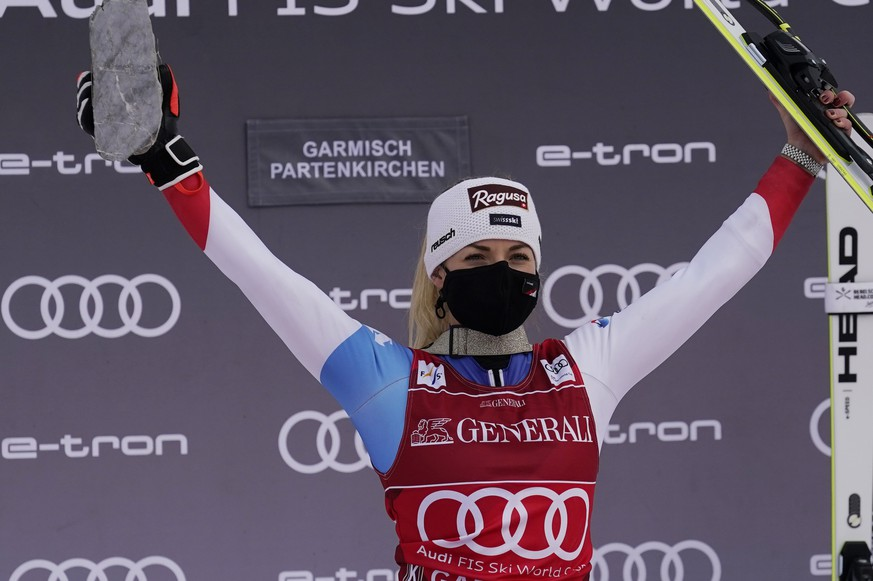 The winner, Switzerland's Lara Gut-Behrami celebrates on podium after completing an alpine ski, women's World Cup super-G race in Garmisch-Partenkirchen, Germany, Saturday, Jan. 30, 2021. (AP Photo/Giovanni Auletta)