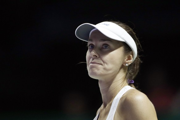 Martina Hingis of Switzerland, paired with partner Chan Yung-jan of Taiwan, reacts after conceding a point to Timea Babos of Hungary and Andrea Hlavackova of the Czech Republic during their doubles semifinal match at the WTA tennis tournament in Singapore, on Saturday, Oct. 28, 2017. (AP Photo/Yong Teck Lim)