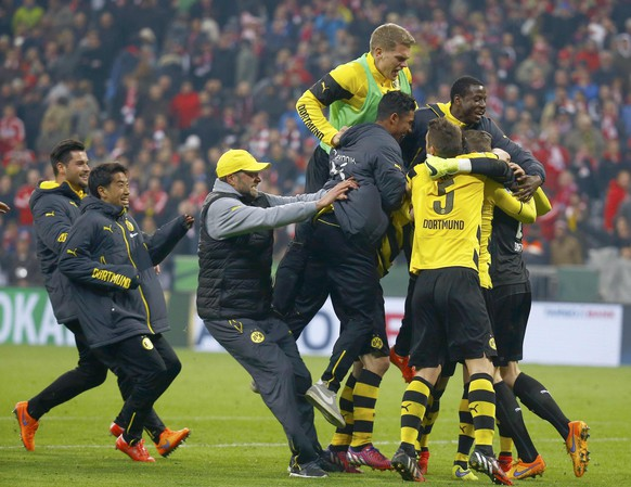 Borussia Dortmund players and coach Juergen Klopp (3rd L) celebrate after defeating Bayern Munich in the German Cup (DFB Pokal) semi-final soccer match in Munich, Germany April 28, 2015. Dortmund won the match 2-0 on penalties.     REUTERS/Kai Pfaffenbach TPX IMAGES OF THE DAY DFB RULES PROHIBIT USE IN MMS SERVICES VIA HANDHELD DEVICES UNTIL TWO HOURS AFTER A MATCH AND ANY USAGE ON INTERNET OR ONLINE MEDIA SIMULATING VIDEO FOOTAGE DURING THE MATCH.