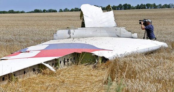 epa04392084 (FILE) A file picture dated 20 July 2014 shows a cameraman filming a detail of the empennage tail debris at the main crash site of Boeing 777 Malaysia Airlines flight MH17 in the eastern Ukraine region near Grabovo, some 100 Km east from Donetsk, Ukraine. Malaysia Airlines Flight MH17 crashed after breaking up in the air probably after being hit 'by a large number of high-energy objects,' a preliminary Dutch investigative report released on 09 September 2014 finds. Images of the MH17 wreckage show that it was pierced in numerous places from the outside, causing the Boeing 777 to break up in flight over eastern Ukraine, the preliminary Dutch investigative report says. Investigators found no evidence that the crash resulted from a technical problem or crew error, says the report by the Dutch Safety Board.  EPA/ROBERT GHEMENT *** Local Caption *** 51489327