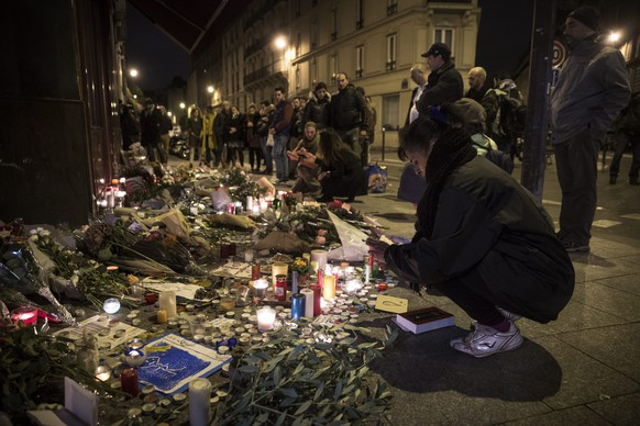 epa05025858 People place flowers and light candles in tribute for the victims of the 13 November Paris attacks at the Carillon Cafe in Paris, France, 14 November 2015. At least 129 people have been killed in a series of attacks in Paris on 13 November, according to French officials.  EPA/ETIENNE LAURENT