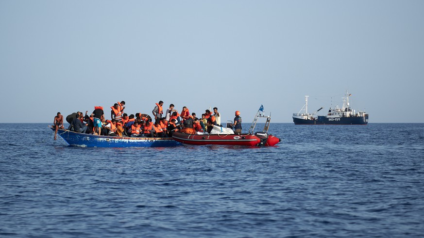 epa07704799 A handout photo made available by German civil sea rescue organisation sea-eye shows a boat carrying migrants (L) and a rescue boat of sea-eye, in the Mediterranean Sea, 08 July 2019 (issued 09 July 2019). According to sea-eye, 44 people were rescued from a woodden boat floating in the Mediterranean between Malta and Lampedusa. The migrants were taken onboard the Alan Kurdi rescue vessel operated by sea-eye and are expected to be transferred to land by the Maltese Navy.  EPA/FABIAN HEINZ / SEA-EYE HANDOUT  HANDOUT EDITORIAL USE ONLY/NO SALES