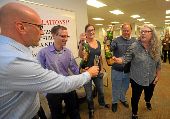 From left, Daily Breeze publisher Ron Hasse, Rob Kuznia, Rebecca Kimitch, Frank Suraci and Toni Sciaqua celebrate in the newsroom after winning the Pulitzer Prize for local reporting in Torrance, Calif., Monday, April 20, 2015. The paper won the Pulitzer Prize for local reporting Monday for a series of stories exposing corruption and cronyism in a small, cash-strapped Southern California school district whose superintendent was ultimately fired. (Scott Varley/The Daily Breeze via AP)
