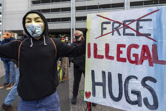 Ein Teilnehmer mit einem Plakat an der Kundgebung fuer die Verhaeltnismaessigkeit der Corona-Massnahmen in Basel am 7. November, 2020. (KEYSTONE/Georgios Kefalas)