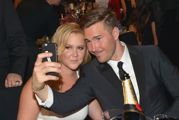 SANTA MONICA, CA - JANUARY 17:  Honoree Amy Schumer (L) and designer Ben Hanisch pose for a selfie photo at the 21st Annual Critics' Choice Awards presented by FIJI Water at Barker Hangar on January 17, 2016 in Santa Monica, California.  (Photo by Charley Gallay/Getty Images for FIJI Water)