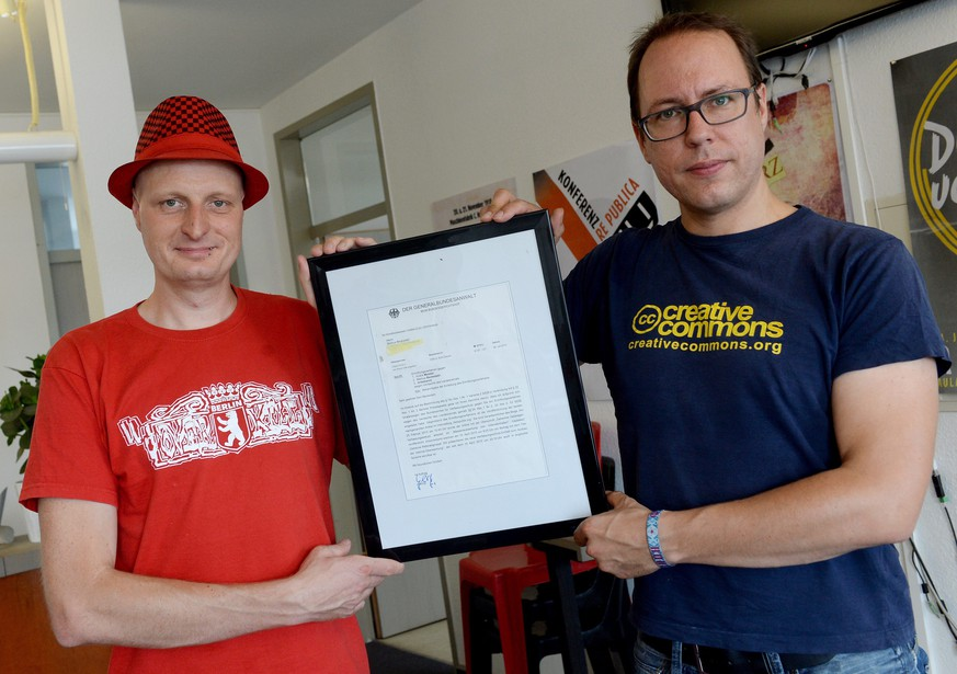 epa04871740 Journalists Markus Beckedahl (L) and Andre Meister (R) pose with a letter from the Attorney General notifying them of the treason investigation opened against them, in the editorial office of the Netzpolitik.org blog in Berlin, Germany, 04 August 2015. The two journalists are being investigated for treason relating to two articles they posted on the technology used by a German intelligence agency for surveillance of social networks, though according to reports the probe has been momentarily paused amid wide spread criticism it undermines press freedom.  EPA/BRITTA PEDERSEN