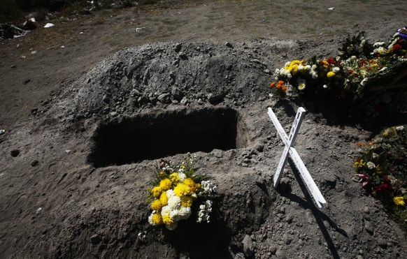 """A grave is empty next to graves with fresh flowers on them at the Valle de Chalco municipal cemetery amid the new coronavirus pandemic, on the outskirts of Mexico City, Friday, Oct. 30, 2020. Mexican families traditionally flock to local cemeteries to honor family members who died as part of the """"Day of the Dead"""" holiday, every Nov. 1 and 2, but according to authorities cemeteries will be closed this year to help slow the spread of COVID-19. (AP Photo/Marco Ugarte)"""