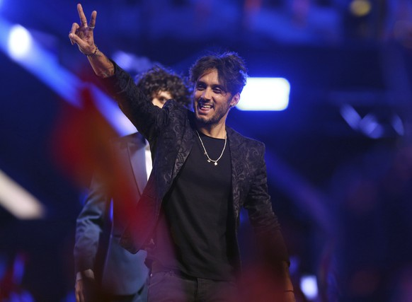 Ermal Meta and Fabrizio Moro from Italy gesture as they arrive on stage in Lisbon, Portugal, Saturday, May 12, 2018 before the Eurovision Song Contest grand final. (AP Photo/Armando Franca)