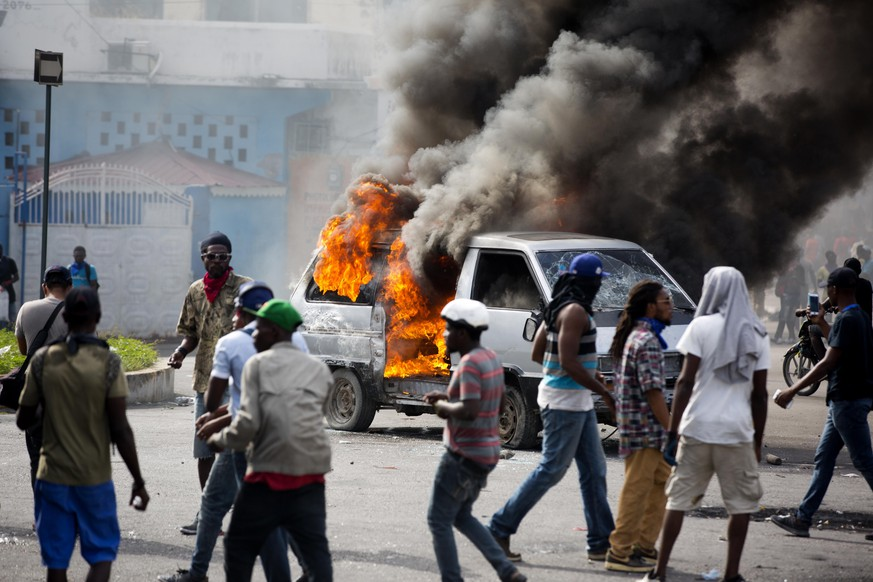 Smoke billows from a van set fire by protesters during clashes with police amid a protest demanding the resignation of Haitian President Jovenel Moise near the presidential palace in Port-au-Prince, Haiti, Tuesday, Feb. 12, 2019. Protesters are angry about skyrocketing inflation and the government's failure to prosecute embezzlement from a multi-billion Venezuelan program that sent discounted oil to Haiti. (AP Photo/Dieu Nalio Chery)