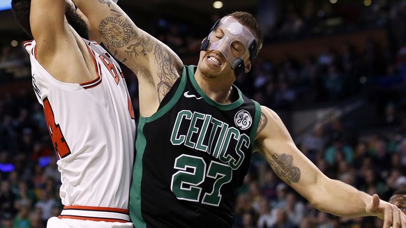 Boston Celtics' Daniel Theis (27) reaches for the ball over Chicago Bulls' Nikola Mirotic during the second quarter of an NBA basketball game in Boston Saturday, Dec. 23, 2017. (AP Photo/Winslow Townson)