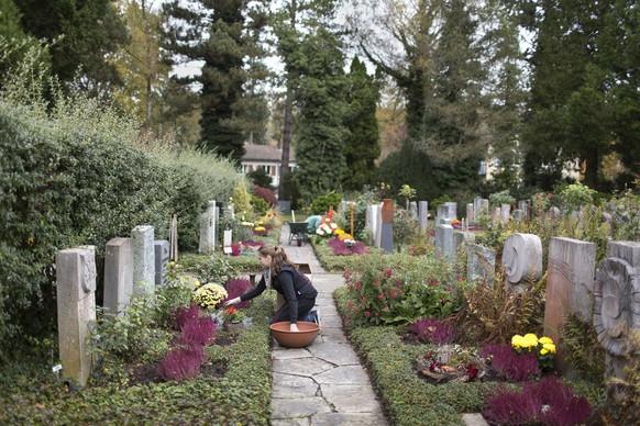 ZUM ALLERHEILIGEN DIESEN SAMSTAG, 1. NOVEMBER, STELLEN WIR IHNEN FOLGENDES NEUE BILDMATERIAL ZUR VERFUEGUNG --- Florists decorate a grave, pictured in the cemetery Enzenbuehl  in Zurich, Switzerland, on October 30, 2014 (KEYSTONE/Gaetan Bally)
