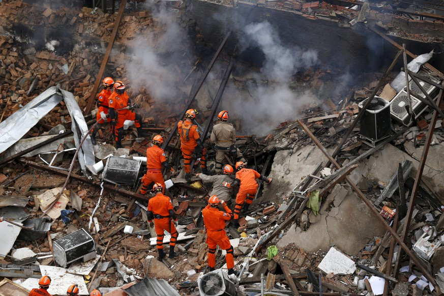 Rescue workers remove debris after an explosion at a few commercial establishments in Rio de Janeiro, Brazil, October 19, 2015. A gas leak is said to be the most likely cause for the explosion which left seven injured so far. Rescue workers are continuing their efforts in searching for any survivors under the rubble, according to local media. REUTERS/Pilar Olivares