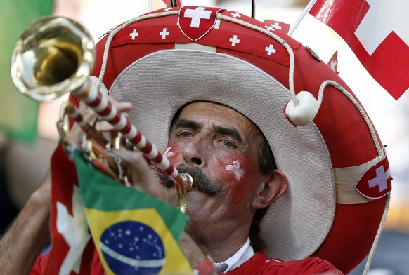 Swiss supporter Sigfried Michel, aka Trompeten Sigi or Trumpet Sigi, plays the trumpet prior to the group E preliminary round match between Switzerland and France in the Arena Fonte Nova in Salvador, Brazil, Friday, June 20, 2014. (KEYSTONE/Peter Klaunzer)....RESTRICTIONS APPLY: Editorial Use Only, not used in association with any commercial entity - Images must not be used in any form of alert service or push service of any kind including via mobile alert services, downloads to mobile devices or MMS messaging - Images must appear as still images and must not emulate match action video footage - No alteration is made to, and no text or image is superimposed over, any published image which: (a) intentionally obscures or removes a sponsor identification image; or (b) adds or overlays the commercial identification of any third party which is not officially associated with the FIFA World Cup.