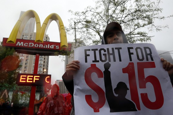 Demonstrators protest in front of a McDonald's restaurant in Chicago, Illinois, May 15, 2014. U.S. fast food workers seeking higher wages plan strikes and demonstrations on Thursday that could affect thousands of restaurants across the country the workers say make huge profits from paying them workers a pittance. REUTERS/Jim Young (UNITED STATES - Tags: BUSINESS EMPLOYMENT)