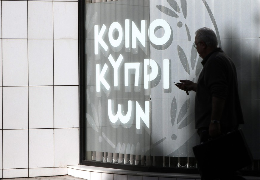 epa04531021 A man walk outside a branch of Bank of Cyprus in Nicosia,16 December 2014. The Bank of Cyprus shares begin trading ?n the Cyprus Stock Exchange and the Athens Stock Exchange today, after 21 months of suspension, marking an additional step towards the stabilisation of Cyprus` largest lender. The total issued share capital of the Bank is 892.2 million euros, divided into 8,922,377,345 ordinary shares of a nominal value of 0.10 euros. The stock price has been set at 0.24 euros. The Bank's stock listing was suspended in March 2013, following the implementation of a 10 billion euro bailout concluded between Cyprus and its international lenders (EC, ECB and IMF).  EPA/KATIA CHRISTODOULOU
