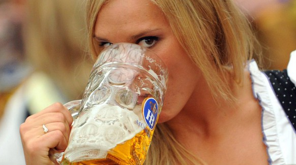 epa01867046 A young woman drinks beer at the annual beer festival 'Oktoberfest' in Munich, Germany, 19 September 2009. The 176th Munich Oktoberfest runs from 19 September to 04 Oktober. Six million visitors are expected.  EPA/ANDREAS GEBERT