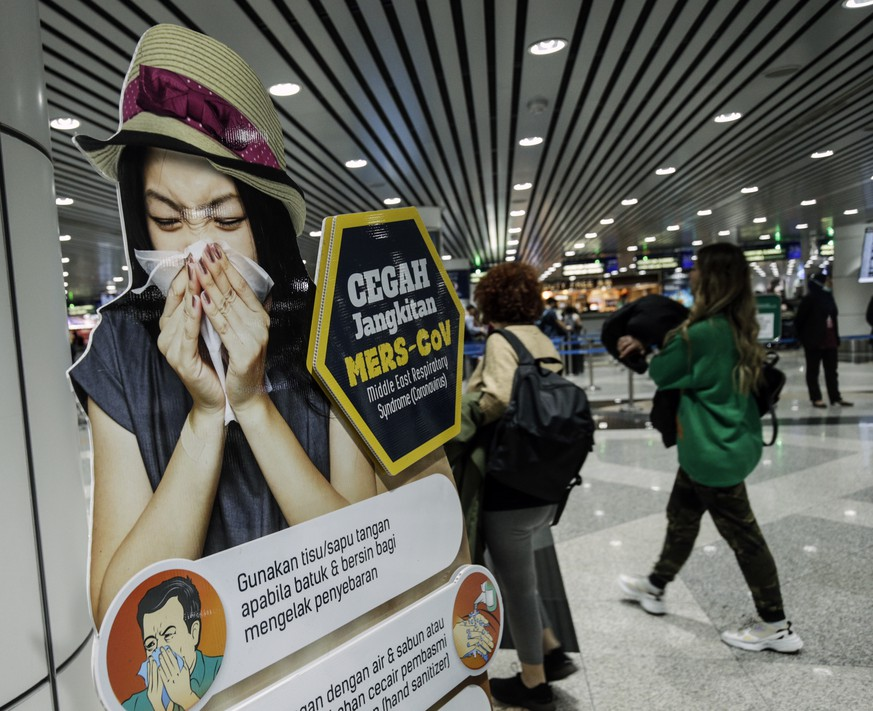 epa08146766 Passengers walk past a poster alerting on coronavirus screening ahead upon their arrival at the Kuala Lumpur International Airport (KLIA) in Sepang, outside Kuala Lumpur, Malaysia, 21 January 2020. More cases of the mysterious SARS-like virus linked to the Wuhan pneumonia outbreak were reported in China on 20 January 2020, bringing the total number of cases to more than 200 with at least six deaths so far.  EPA/AHMAD YUSNI