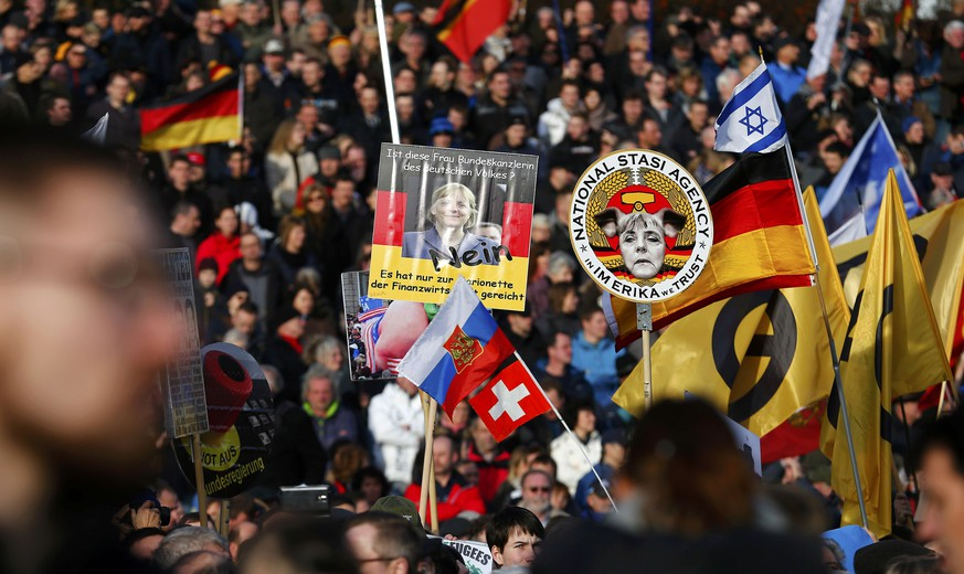 Supporters of the anti-Islam movement Patriotic Europeans Against the Islamisation of the West (PEGIDA) hold posters depicting German Chancellor Angela Merkel during a demonstration in Dresden, Germany, February 6, 2016.  REUTERS/Hannibal Hanschke