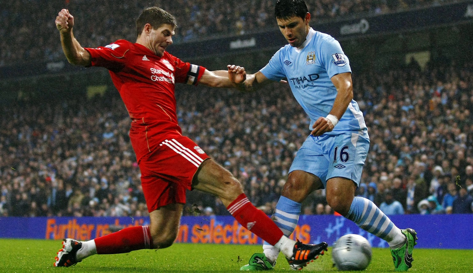 Manchester City's Sergio Aguero, right, vies for the ball against Liverpool's Steven Gerrard during the first leg of their English League Cup semi final soccer match at the Etihad Stadium, Manchester, England, Wednesday Jan. 11, 2012. (AP Photo/Tim Hales)